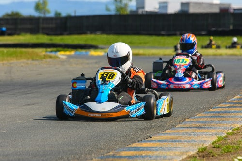 Go Karting track with two brightly coloured karts with people driving them